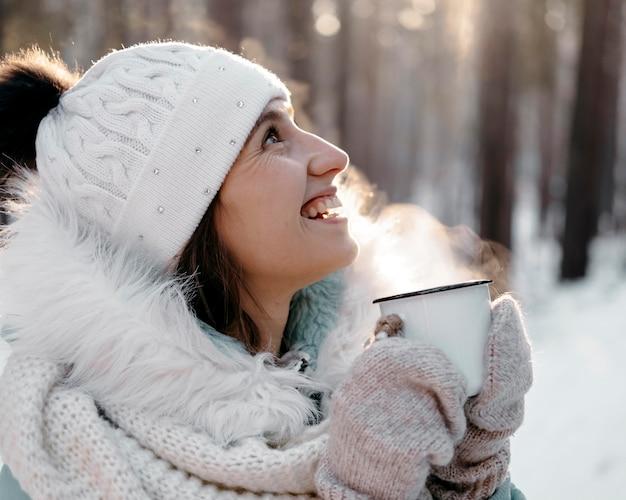 Smileyfrau draußen im winter, die eine tasse tee hält