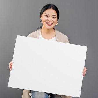 Smileyfrau mit blatt des leeren papiers