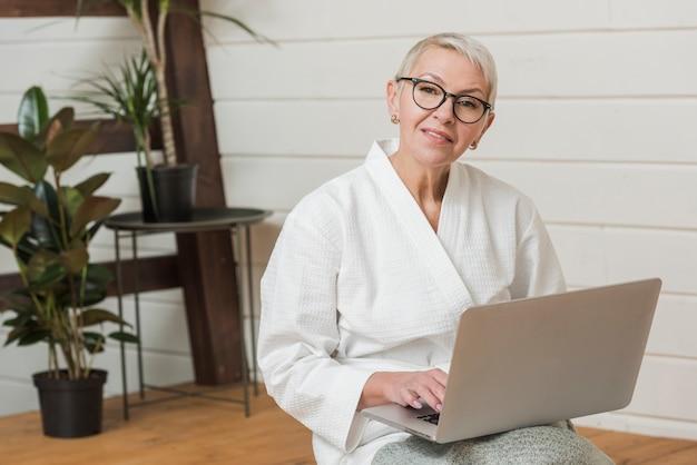 Smileyfrau mit den gläsern, die einen laptop anhalten