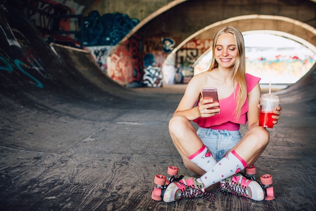 Smileyfrau sitzt aus den grund mit ihren gekreuzten beinen und betrachtet telefon