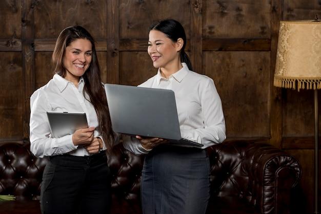 Smileyfrauen, die laptop betrachten