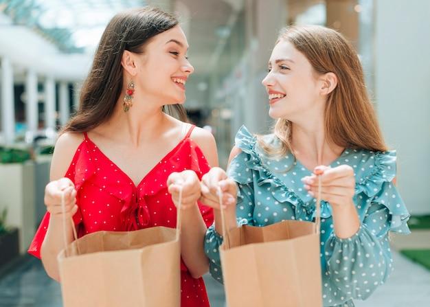 Smileyfreunde, die ihre einkaufstaschen halten