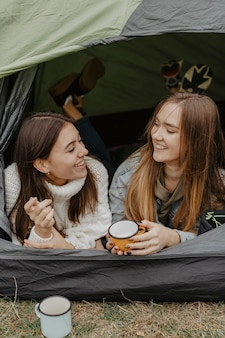 Smileyfreundinnen in trinkendem tee des zeltes