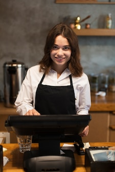 Smileygeschäftsfrau, die am kassierer arbeitet