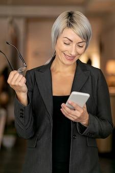 Smileygeschäftsfrau, die telefon betrachtet