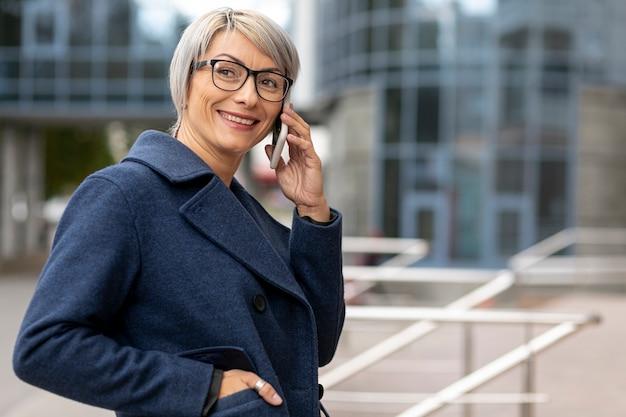 Smileygeschäftsfrau, die über telefon spricht