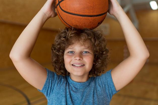 Smileyjunge mit mittlerem schuss, der basketball hält