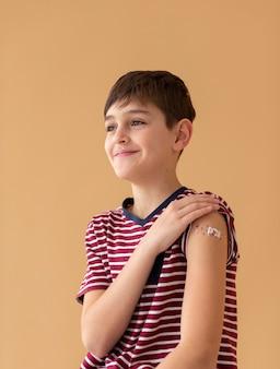 Smileyjunge mit mittlerem schuss nach impfung