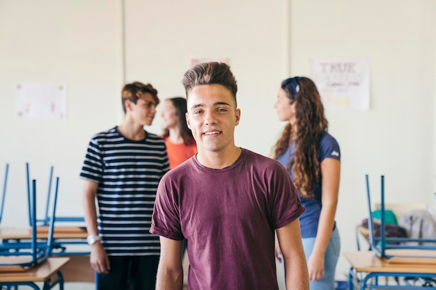 Smileyjunge posiert im klassenzimmer
