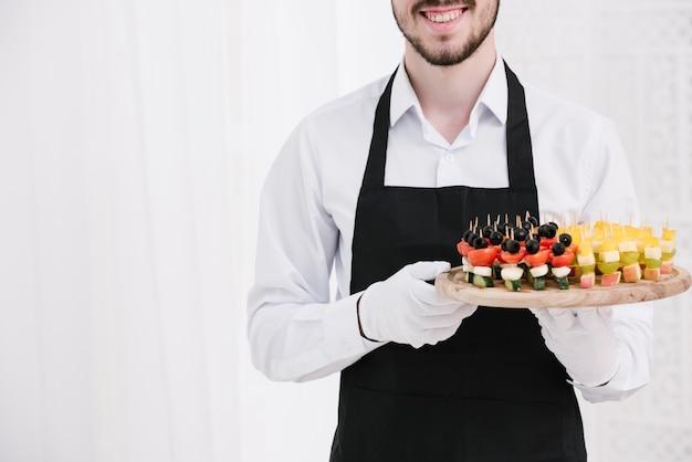Smileykellner, der imbisse auf einer platte hält