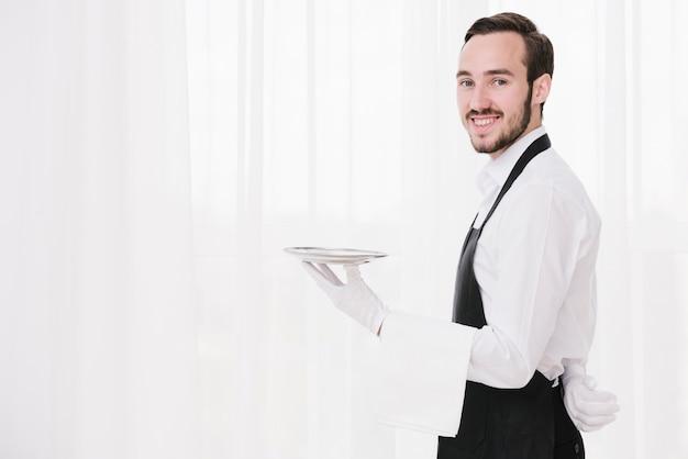 Smileykellner mit der platte, die kamera betrachtet