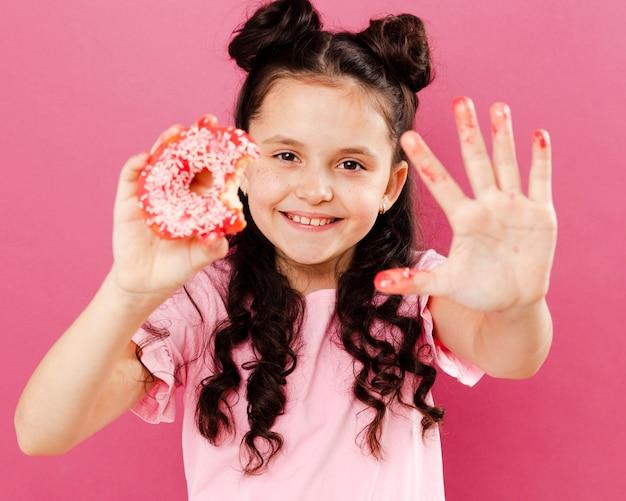 Smileymädchen, das glasierte hand vom donut zeigt