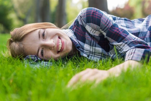 Smileymädchen, das kamera beim bleiben auf gras betrachtet