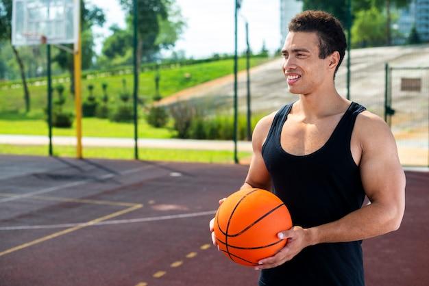 Smileymann, der einen ball auf dem basketballplatz hält