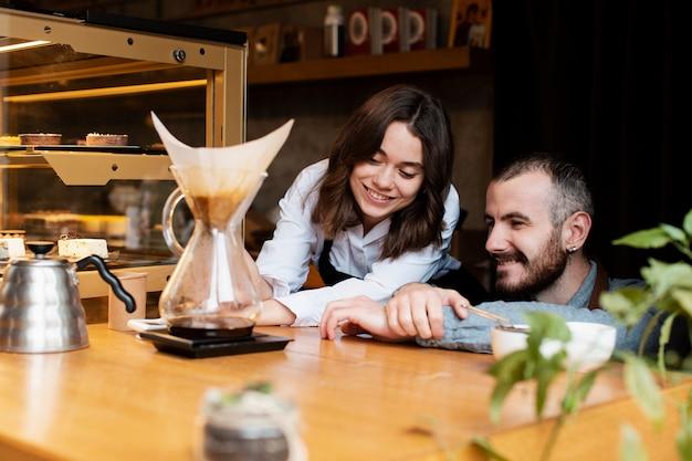 Smileypaare, die kaffeefilter betrachten