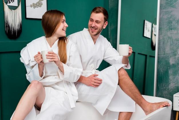 Smileypaare in den bademäntel, die schalen halten