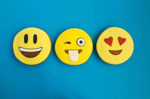 Smileys in form von lebkuchen auf dem blauen hintergrund. draufsicht. closeup. kopierraum.