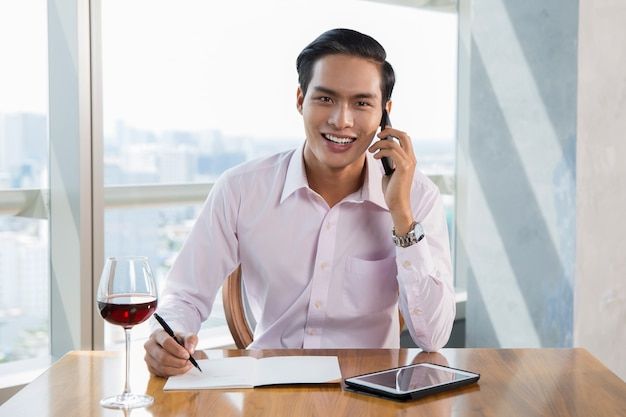 Smiling asiatischen geschäftsmann am smartphone