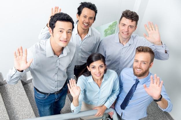 Smiling business team winken auf office treppenhaus