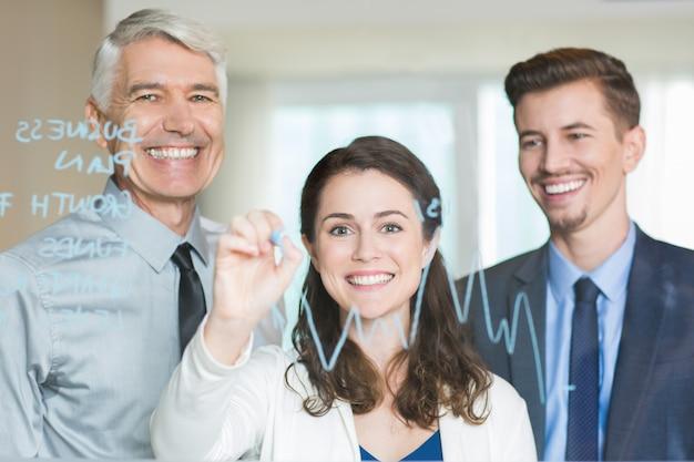 Smiling business team zeichnung diagramm auf glasschirm