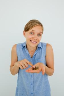 Smiling doubtful woman zählen münzen auf palm