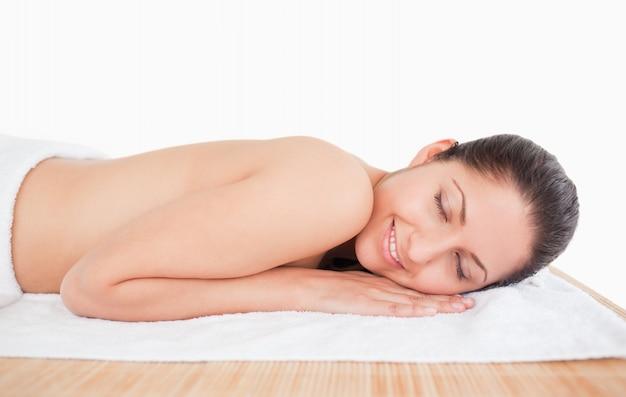 Smiling dunkelhaarige junge frau auf einem massagetisch
