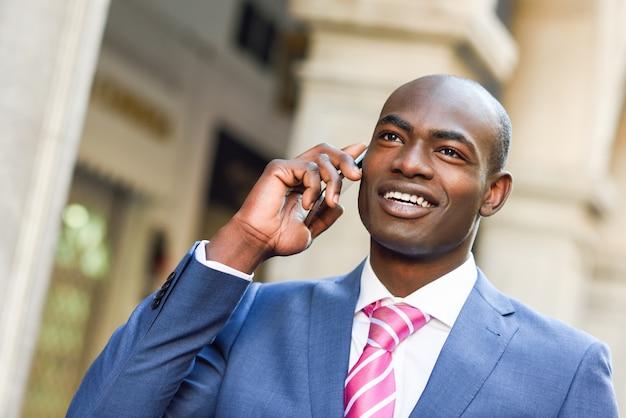 Smiling geschäftsmann im gespräch mit seinem smartphone