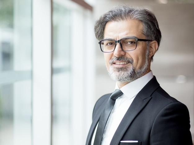 Smiling middle-aged business leader am fenster