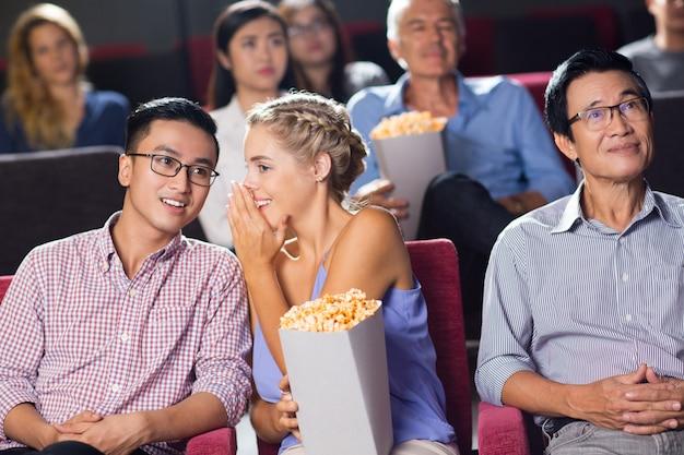 Smiling multiethnischen junge paar in kino sitzen