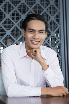 Smiling young asian man sitzt im restaurant