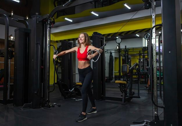 Smilling fit frau, die muskeln auf fitnessgerät biegt. mädchen führen übung mit der übungsmaschine cable crossover in der modernen turnhalle durch. fitness und bodybuilding