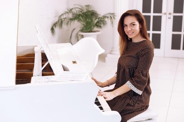 Smilling junge frau, die am klavier sitzt