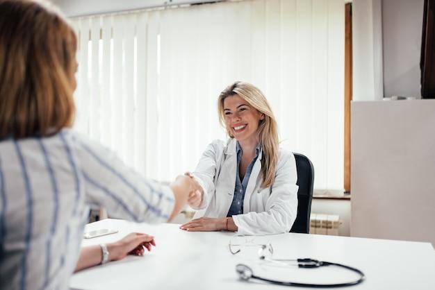 Smling ärztinhändedruck mit einem patienten.