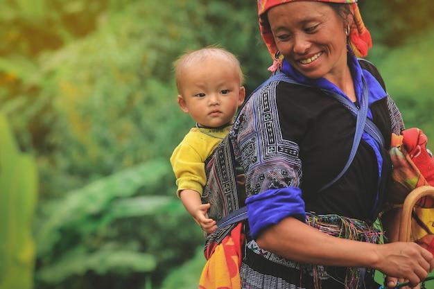 Smling hmong-stammfrau, die ihr kind in ihrem rucksack in mu-cang chai nordvietnam trägt