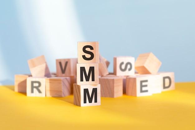 Smm geschrieben auf holzwürfeln - angeordnet in einer vertikalen pyramide, grauem und gelbem hintergrund, smm - kurz für social media marketing, geschäftskonzept