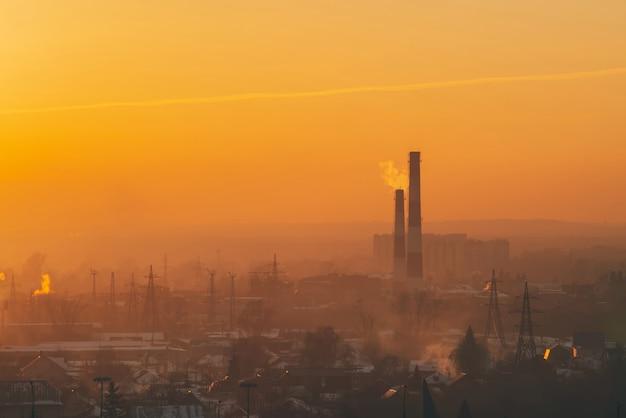 Smog unter silhouetten von gebäuden am sonnenaufgang. schornstein im dämmerungshimmel. umweltverschmutzung am sonnenuntergang. schädliche dämpfe vom stapel über stadt. städtischer hintergrund des nebels mit warmem himmel des orange gelbs.