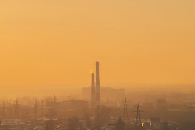 Smog unter silhouetten von gebäuden bei sonnenaufgang. schornstein im morgenhimmel. umweltverschmutzung bei sonnenuntergang. schädliche dämpfe vom stapel über der stadt.