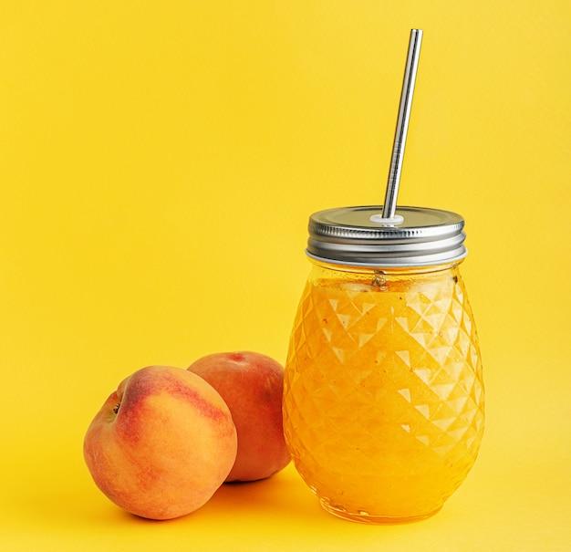 Smoothie-glas mit reifen saftigen pfirsichen an der gelben wand.