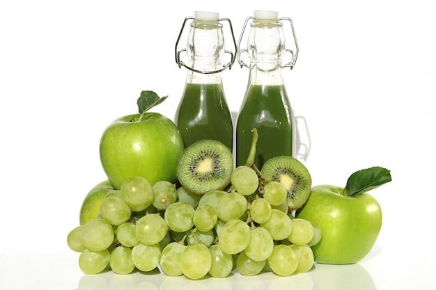 Smoothie. grüner vegetarischer frucht smoothie in den glasflaschen und in sortierten grünen früchten