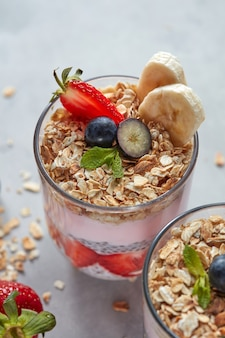 Smoothie in gläsern mit früchten erdbeere, banane, blaubeere, haferflocken und chia