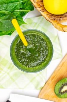Smoothie mit frischen spinatblättern, apfel und kiwi im glas mit trinkhalm, vertikale draufsicht.