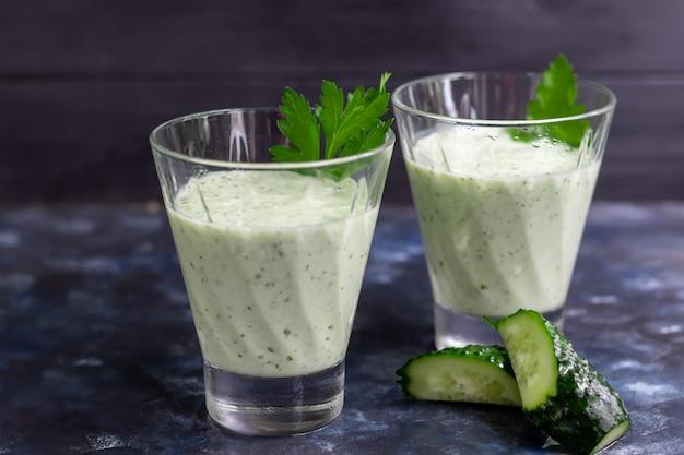 Smoothie mit gurke, petersilie und kefir auf einem dunklen tisch. gesunde ernährung, ernährung.
