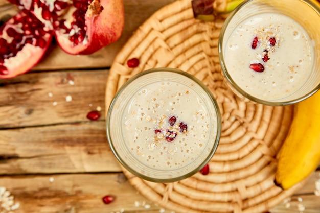 Smoothie mit hafer oder haferflocken, banane und granatapfel auf rustikalem holzhintergrund.