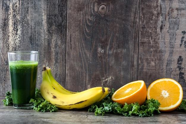 Smoothie mit kohl, banane und orange auf hölzernem hintergrund