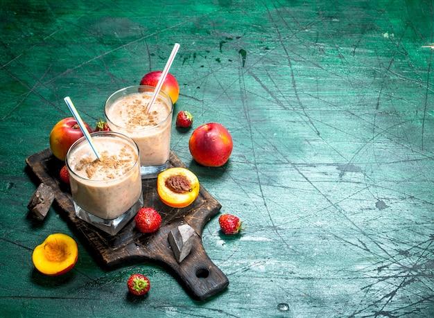 Smoothie mit pfirsichen, erdbeeren und schokolade. auf rustikalem hintergrund.