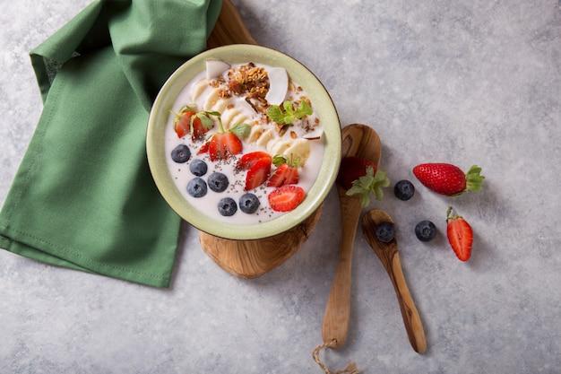 Smoothie oder smoothy bowl mit müsli, früchten und samen. bio-getränk oder joghurt mit erdbeere, auf dem weißen grauen hintergrund. darmgesundheit. fermentiertes milchgetränk. trendiges essen. speicherplatz kopieren