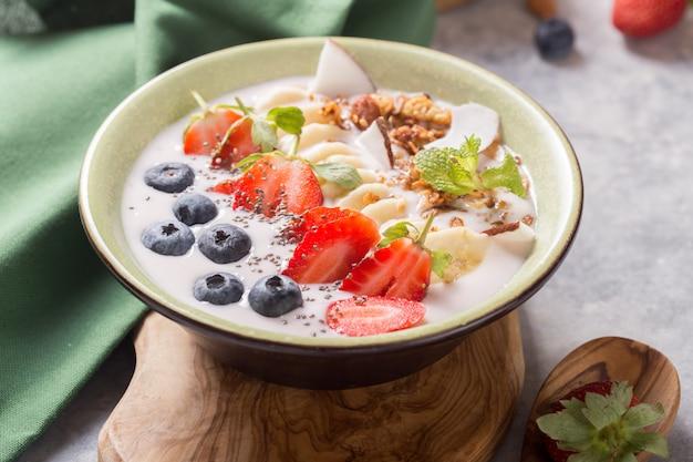 Smoothie oder smoothy bowl mit müsli, früchten und samen. bio-getränk oder joghurt mit erdbeere