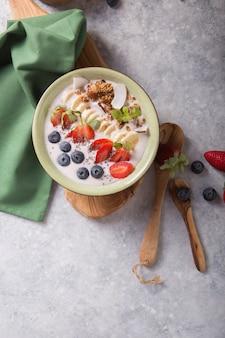Smoothie oder smoothy bowl mit müsli, früchten und samen. bio probiotisches getränk oder joghurt mit erdbeere, auf dem weißen grauen hintergrund. darmgesundheit. fermentiertes milchgetränk. trendiges essen.