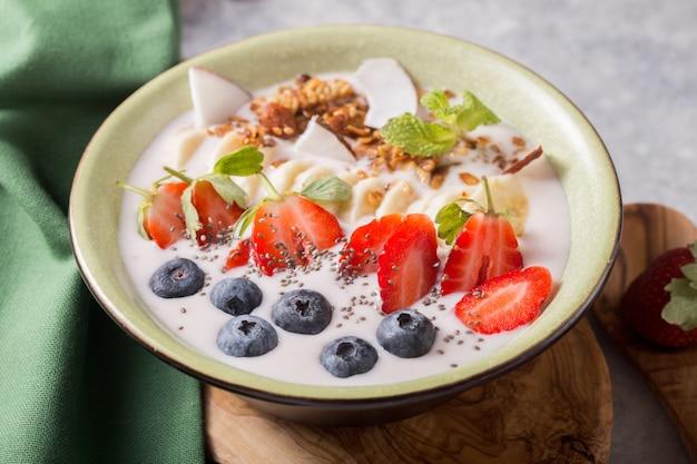 Smoothie oder smoothy bowl mit müsli, früchten und samen. bio probiotisches getränk oder joghurt mit erdbeere
