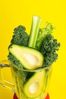 Smoothie-rezept. grüner smoothie des gemüses (avocado, sellerie, kohlsalat, spinat) in einer mischmaschine auf einem gelben hintergrund. veganes und gesundes lebensmittelentgiftungskonzept